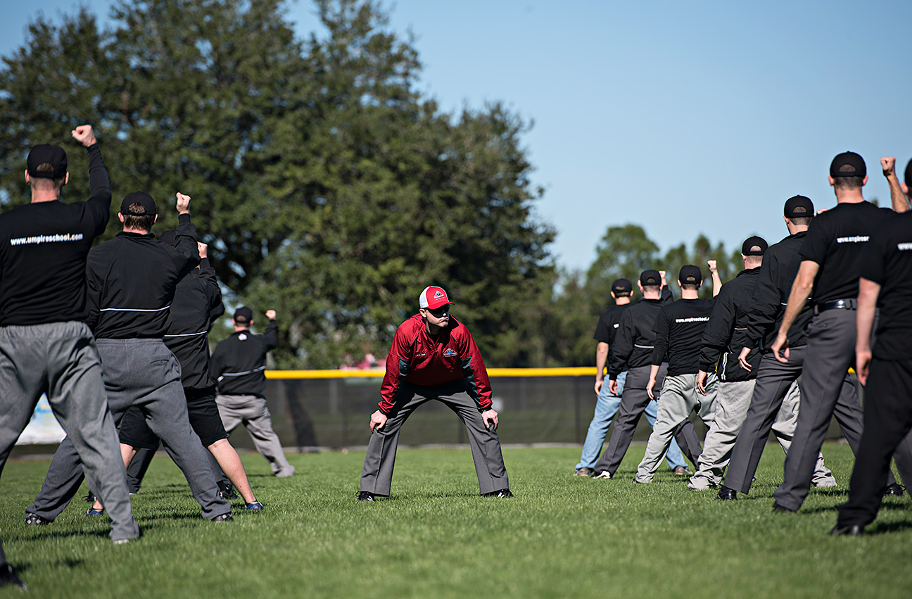 DAYTONA BEACH, FL - JANUARY 4, 2016:  Squatting down between rows of would-be umpires, instructor Darius Ghani keeps an eye on their mechanics as they learn how to call a proper strike at the Harry Wendelstedt Umpire School in Daytona Beach, Fla. (Photo by Melissa Lyttle)